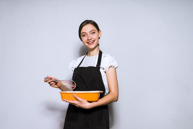 Cuoco unico felice della giovane donna in grembiule nero che prepara un pasto delizioso per cena