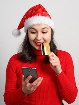 Felice giovane donna in un berretto di natale e un maglione rosso tiene uno smartphone e una carta di credito su bianco.