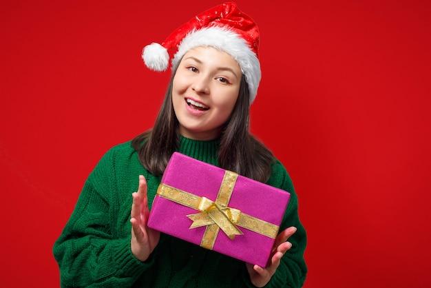 Felice giovane donna in protezione di natale con regalo su sfondo rosso