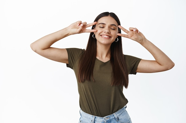 Felice giovane donna chiude gli occhi e sorride sognante, mostrando il segno della discoteca v, gesto di pace sul viso, in piedi gioiosa contro il muro bianco