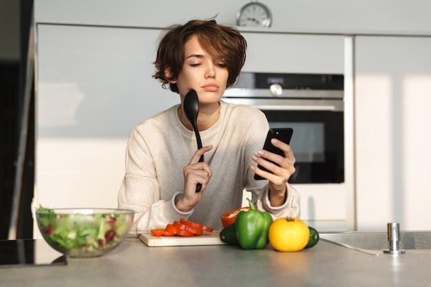 Felice giovane donna che cucina insalata fresca in cucina a casa