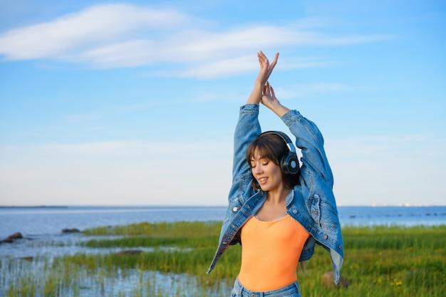 Felice giovane donna che balla in cuffie sulla riva del sole della baia soleggiata giornata di primavera