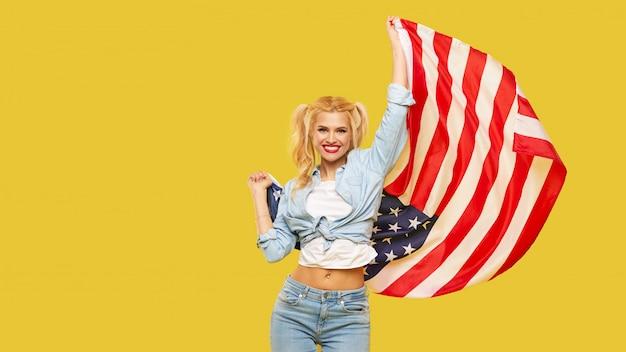 La giovane donna felice in denim copre la tenuta della bandiera di usa su fondo giallo. banner. copia spazio per il testo.