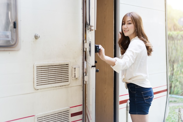 Felice giovane donna alla porta di un camper rv van motorhome