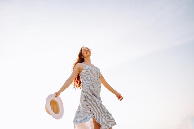 Felice giovane donna in abito e cappello di paglia e camminare da solo sulla spiaggia di sabbia vuota al tramonto in riva al mare e sorridente.