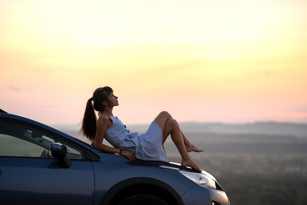 Felice giovane donna autista in abito blu posa sul suo cofano per auto godendo una calda giornata estiva.