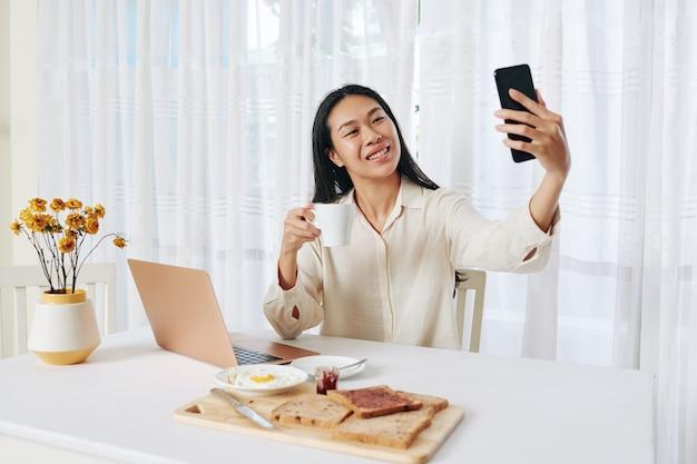 Giovane donna felice che mangia prima colazione e che fa telefonata di affari alla sua scrivania nel soggiorno
