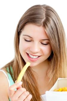 Giovane donna felice che mangia le patate fritte