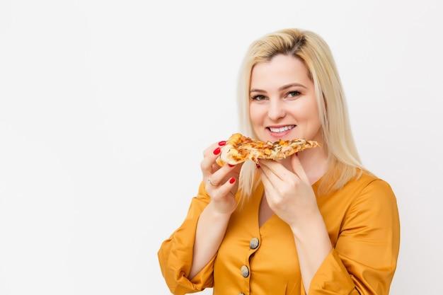 Felice giovane donna che mangia una fetta di pizza calda, isolata su bianco