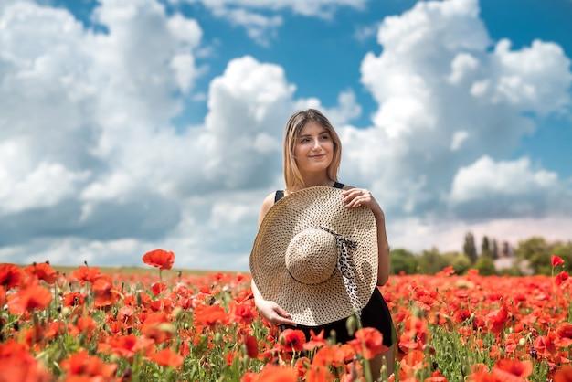 Giovane donna felice che gode della libertà alla natura, campo del papavero. estate