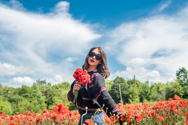 Giovane donna felice che gode della libertà alla natura sul campo del papavero