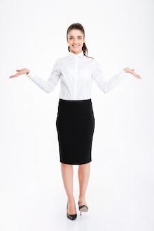 Felice giovane donna in abiti da cerimonia che tiene lo spazio della copia in entrambe le mani mentre sta in piedi isolato su bianco