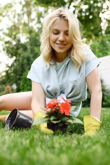 La giovane donna felice in guanti lavora con il fiore nel giardino