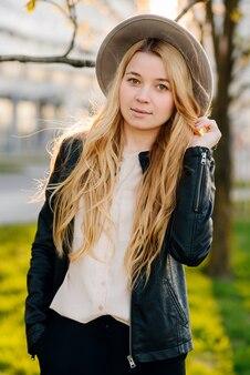 Giovane donna felice in cappello che cammina nella città di estate