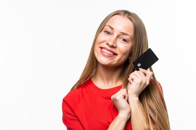 La giovane donna felice tiene la carta di credito isolata sulla superficie bianca