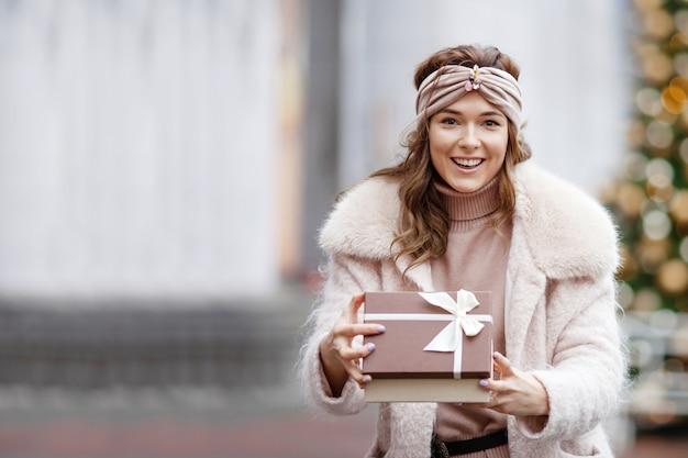 Felice giovane donna in possesso di un regalo su un mercatino di natale. è ora di fare regali. concetto di shopping natalizio e regali di natale. copia spazio