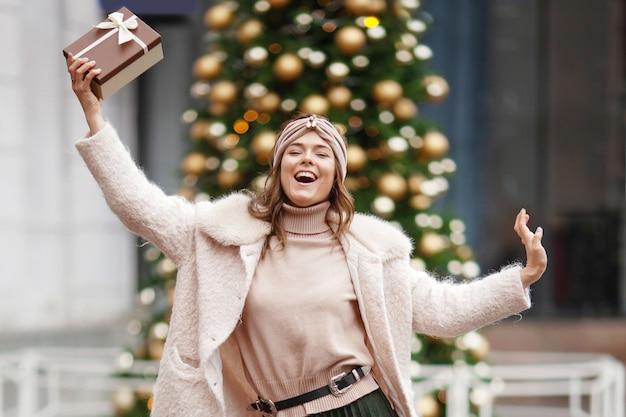 Felice giovane donna in possesso di un regalo su un mercatino di natale. è ora di fare regali. concetto di shopping natalizio e regali di natale