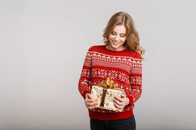 Giovane donna felice che tiene un regalo