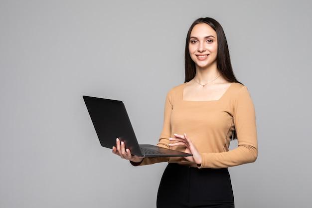 Felice giovane donna che tiene il computer portatile e guarda davanti al muro grigio