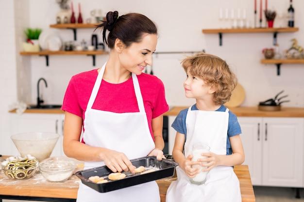 Giovane donna felice che tiene il vassoio con biscotti al forno mentre guarda il suo piccolo figlio e parla con lui in cucina