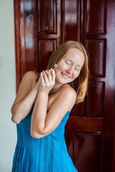 La giovane donna felice tiene la chiave dell'appartamento o della casa. il fortunato vincitore. possedere il concetto immobiliare