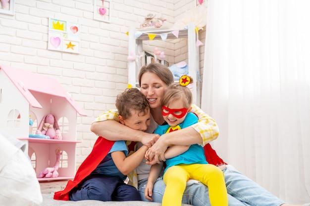 La giovane donna felice sta giocando con i suoi figli mentre i supereroi li abbraccia