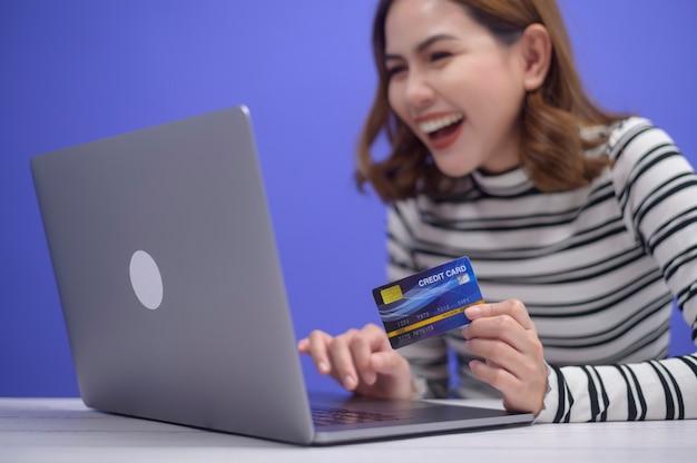 La giovane donna felice sta facendo acquisti online tramite laptop, in possesso di carta di credito credit