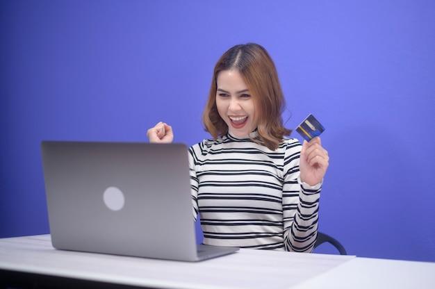 La giovane donna felice sta facendo acquisti online tramite laptop, in possesso di carta di credito
