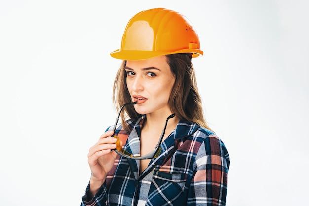 Felice giovane donna indossa casco di sicurezza arancione e camicia a scacchi. guardando la fotocamera, occhiali di sicurezza gialli vicino alle labbra. sfondo isolato.