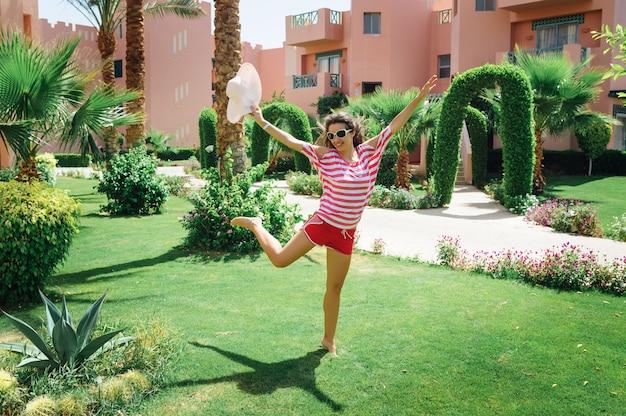 Giovane donna felice che salta nel parco sull'erba