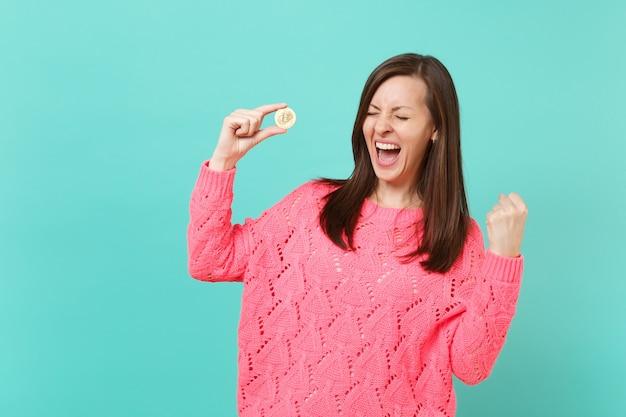 Felice giovane donna in maglia maglione rosa urlando facendo gesto vincitore tenere in mano bitcoin, valuta futura isolata su sfondo blu muro turchese. concetto di stile di vita della gente. mock up copia spazio.