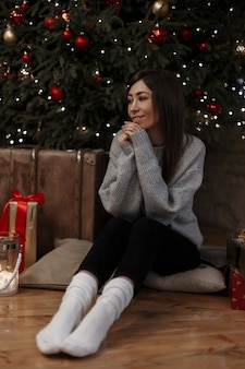 Felice giovane donna in maglione lavorato a maglia in jeans neri in calzini bianchi è seduta sul pavimento vicino all'albero di natale in una stanza accogliente tra le scatole regalo. bella ragazza sogna.
