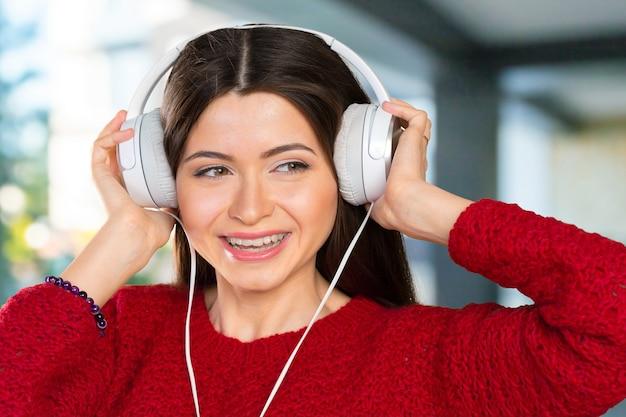 Felice giovane donna che ascolta musica con le cuffie