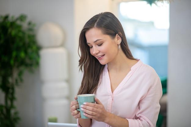 Giovane donna felice che esamina la sua tazza mentre beve il caffè