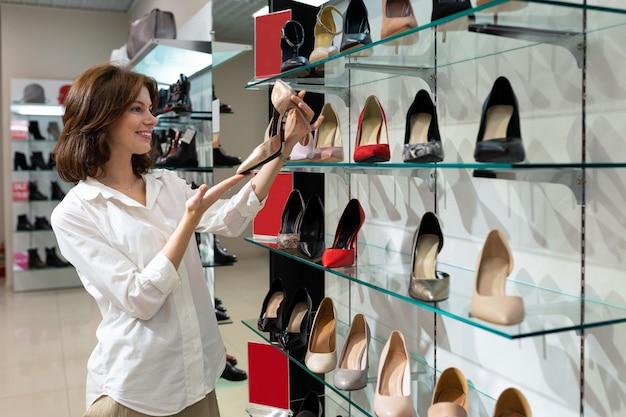 La giovane donna felice esamina le paia delle scarpe in sua mano