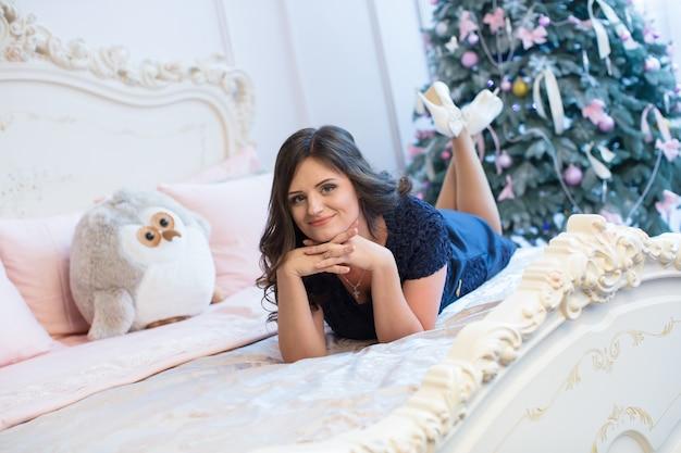 Felice giovane donna sdraiata sul letto sull'albero di natale.