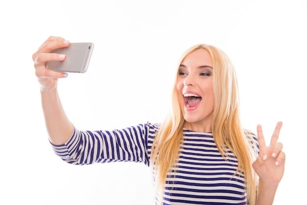 Giovane donna felice che fa selfie divertente con due dita