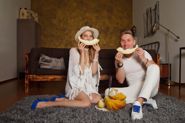 Felice giovane donna e uomo a casa all'interno della stanza con melone. coppia carina con melone in bocca seduto sul pavimento. persone a casa. concetto di colazione in famiglia. spazio di copyright per il sito