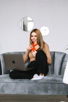 Felice giovane donna regalo di apertura davanti al computer portatile durante la videochiamata o la chat, celebrando online. concetto di relazioni a distanza, feste e stile di vita.