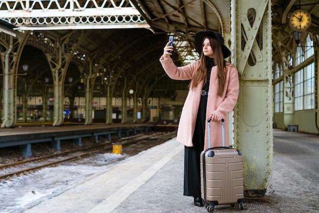 Felice giovane donna sulla piattaforma della stazione ferroviaria in cappotto rosa e cappello nero sta aspettando il treno...