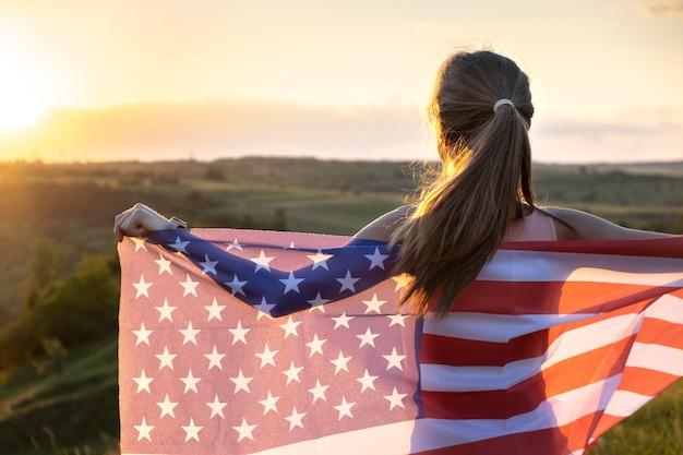 Felice giovane donna in posa con la bandiera nazionale usa in piedi all'aperto al tramonto.