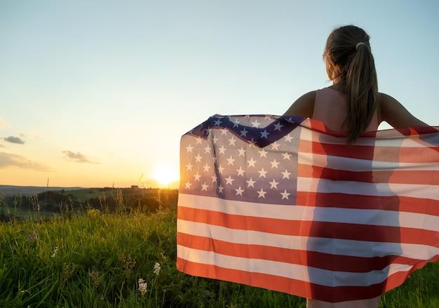 Felice giovane donna in posa con la bandiera nazionale usa in piedi all'aperto al tramonto