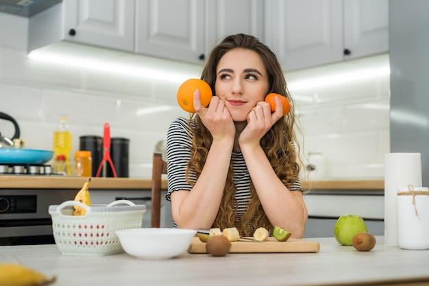 Felice giovane donna prepara facendo macedonia per la dieta in cucina, cibo sano. concetto di dieta.