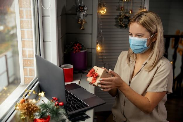 Felice giovane donna in maschera protettiva con un bel regalo nelle sue mani, utilizzando lo zoom per congratularsi con i suoi parenti di buon natale. effettuare videochiamate facetime con il laptop a casa.
