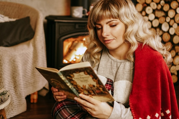 Libro di lettura felice della giovane donna davanti all'interiore di natale con il camino. la ragazza è vestita in abiti accoglienti e accoglienti con un caldo plaid rosso