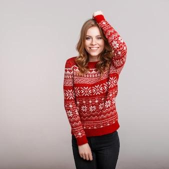 Felice giovane donna in un maglione rosso su sfondo grigio in studio