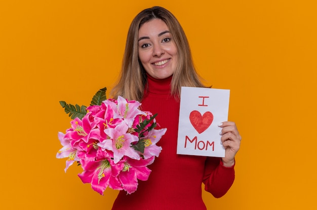 Giovane donna felice in dolcevita rosso che tiene biglietto di auguri e bouquet di fiori. amo la mamma. festa della mamma