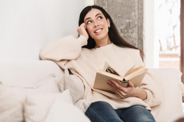 Felice giovane donna rilassante su un divano in soggiorno