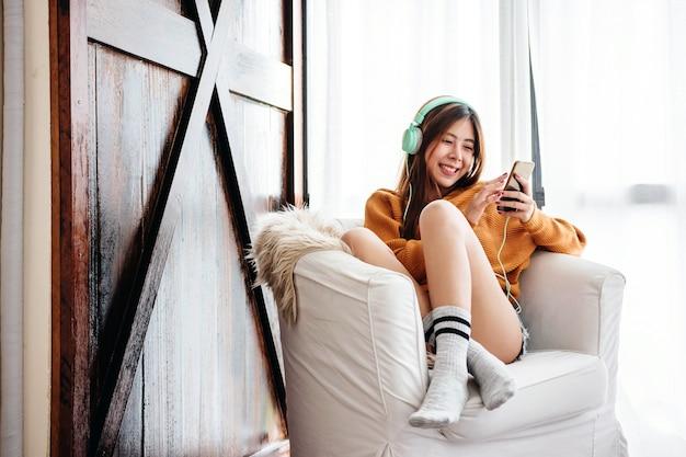 Giovane donna felice che si rilassa con la cuffia di musica sul sofà in camera accogliente