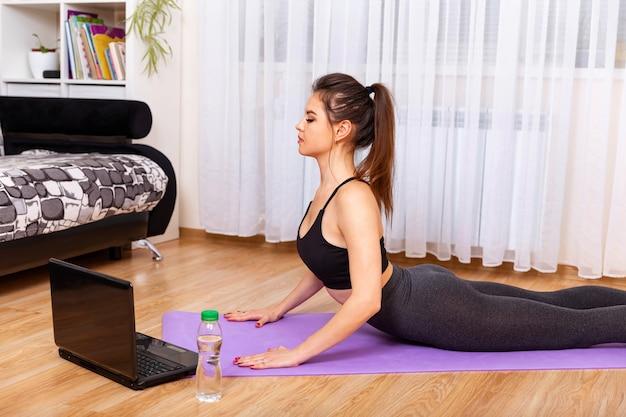 Giovane donna felice che riposa sulla stuoia di yoga che ascolta la musica